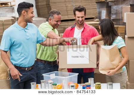 Warehouse workers packing up donation boxes in a large warehouse