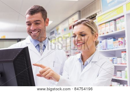 Team of pharmacists looking at computer at the hospital pharmacy