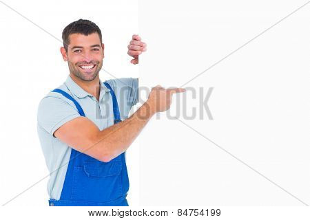 Portrait of smiling repairman in overalls pointing at placard over white background