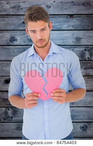Sad man holding a broken heart against wooden background in blue
