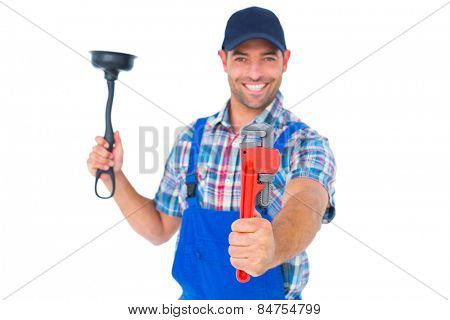 Portrait of handyman holding plunger and wrench on white background