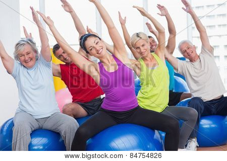 Portrait of happy men and women on fitness balls exercising in gym class