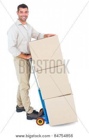 Full length portrait of happy delivery man with trolley of boxes on white background