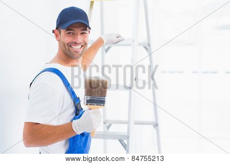 Portrait of happy handyman with paintbrush while climbing ladder at home