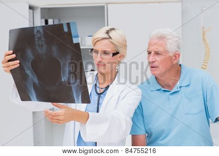 Female doctor and senior patient examining x-ray in clinic