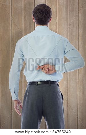 Businessman crossing fingers behind his back against wooden surface with planks