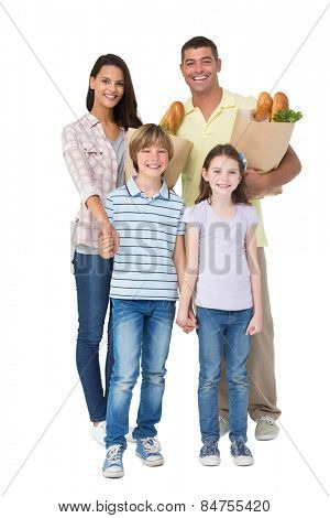 Portrait of happy family with grocery bags over white background