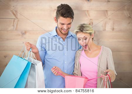 Attractive young couple holding shopping bags against bleached wooden planks background