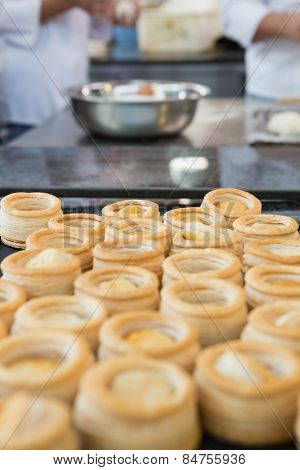 Colleagues making vol-au-vent together in the kitchen of the bakery