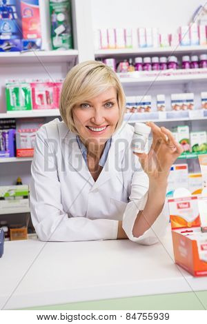 Smiling pharmacist showing medication in the pharmacy