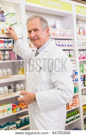 Pharmacist taking medicine from shelf in the pharmacy