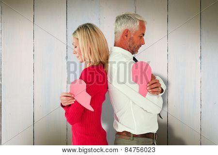 Couple holding two halves of broken heart against wooden planks