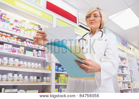 Concentrated doctor reading a prescription in the pharmacy