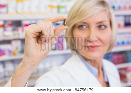 Blonde pharmacist in lab coats showing pill in the pharmacy