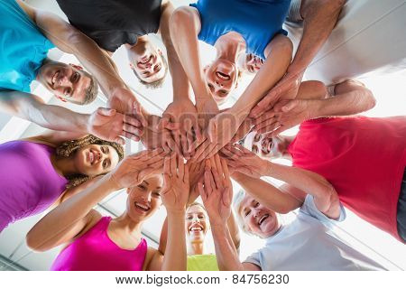 Low angle view of fit people stacking hands at health club