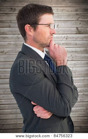 Frowning businessman thinking against wooden planks background