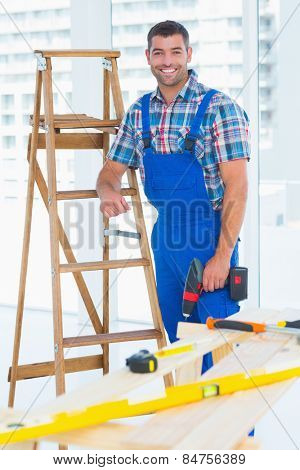 Portrait of smiling male carpenter with power drill standing by ladder at construction site