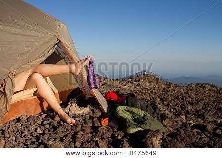 A Woman's Naked Legs Hold A Pair Of Lingerie Outside Of A Tent On A Mountain