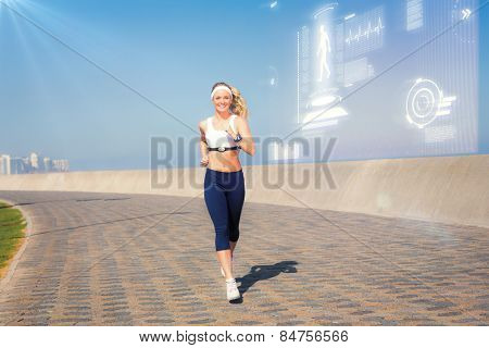 Fit blonde jogging on the pier against fitness interface