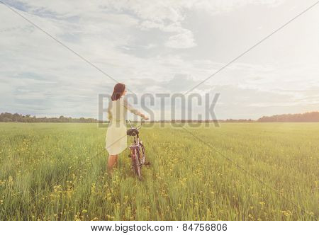 Girl Walking With A Bicycle On Summer Meadow