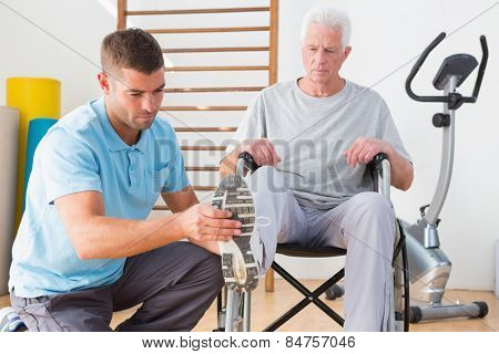 Coach helping invalid senior in fitness studio