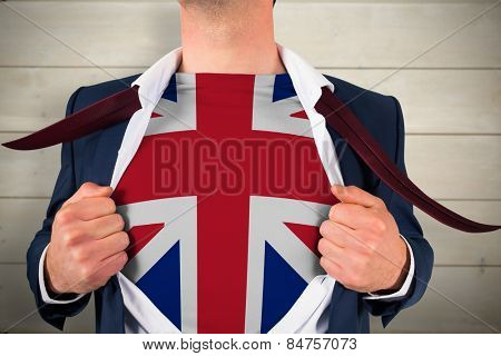 Businessman opening shirt to reveal union jack flag against bleached wooden planks background