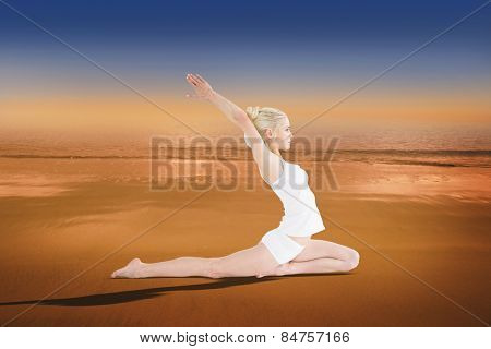 Toned young woman stretching hands backwards against hazy blue sky