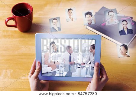 Businesswoman using tablet at desk against serious businessman during a meeting talking to his employees