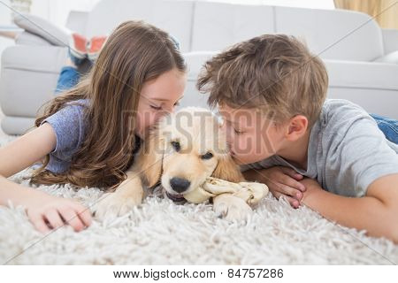 Brother and sister kissing puppy on rug at home