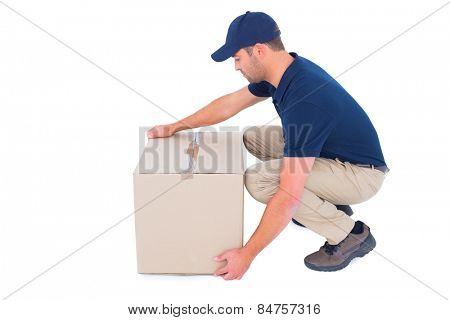 Full length side view of delivery man crouching while picking cardboard box on white background