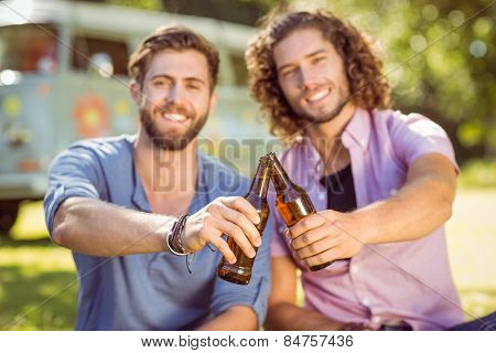 Hipster friends toasting with beers on a summers day