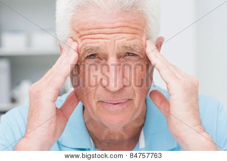 Portrait of senior male patient suffering from headache in clinic