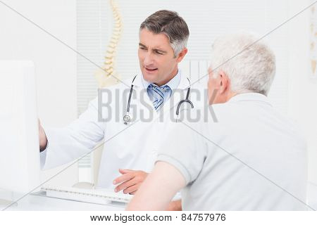 Male doctor explaining reports to senior patient on computer in clinic