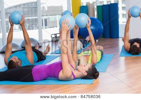Fit people exercising with medicine ball in fitness studio