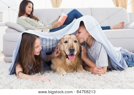Sister looking at brother kissing dog under shawl while mother relaxing on sofa at home