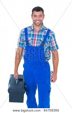 Portrait of happy handyman in coveralls carrying toolbox on white background