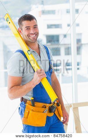 Portrait of happy repairman in overalls holding spirit level in bright office
