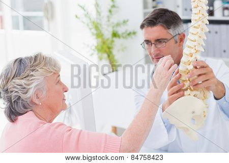 Female patient looking at anatomical spine while doctor explaining her in clinic