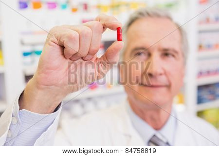 Smiling pharmacist in lab coat showing pill in the pharmacy