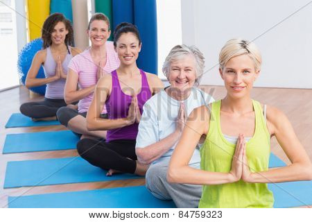 Portrait of happy fit women meditating with hands joined during fitness class