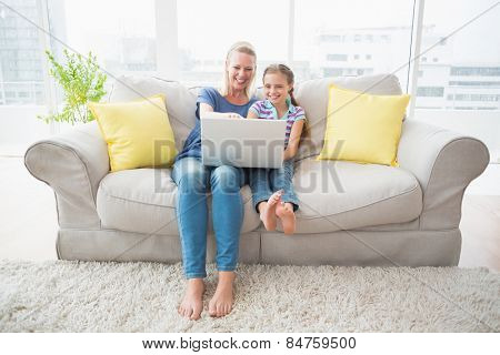 Full length of happy mother and daughter using laptop on sofa at home