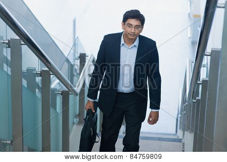Asian Indian corporate businessman in suit with briefcase ascending steps.