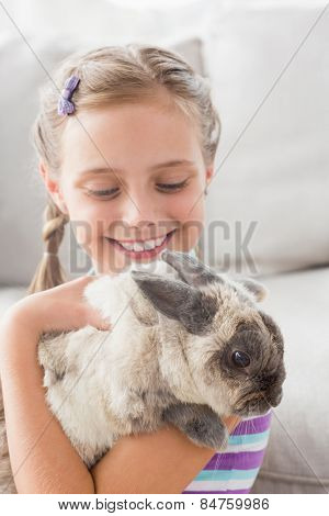 Cute girl playing with rabbit in living room