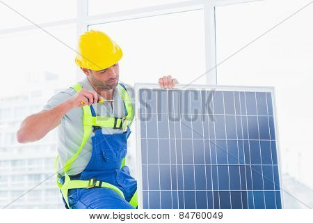 Manual worker tightening solar panel in bright office