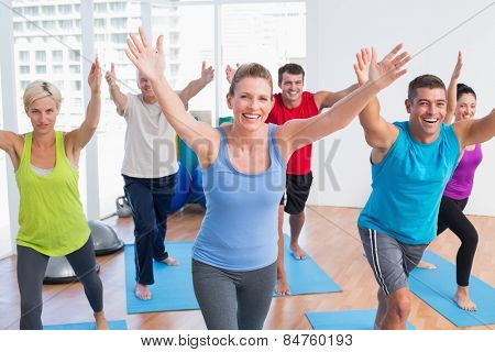 Happy fit men and women exercising in gym class