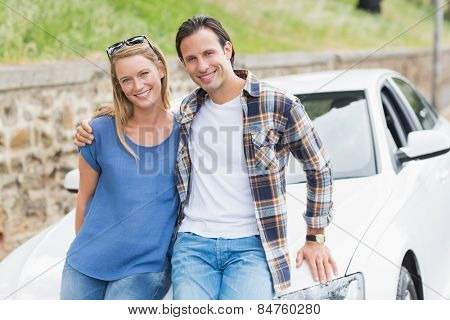 Couple leaning on the bonnet of their car