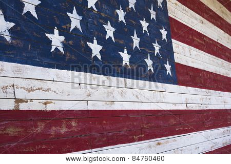 A painting of an American flag on a wood plank wall
