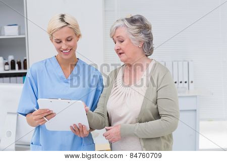 Nurse and senior patient discussing over clipboard in clinic