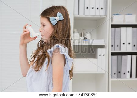 Little girl taking inhaler in medical office