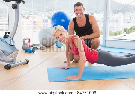 Blonde woman working on exercise mat with her trainer in fitness studio